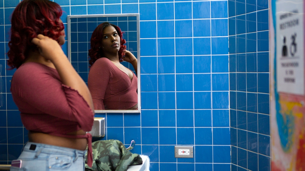 [ID: person wearing jeans, pink top with knot across belly, looking sideways into mirror, reflection of face and upper body visible in mirror, mirror hanging on blue tiled wall, vest in sink beneath mirror]