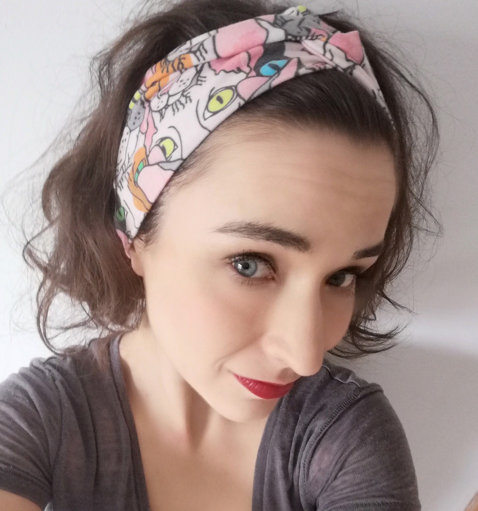 Close up selfie of Alicia looking into the lens, wearing a head band, semi long brown hair backwards, red lipstick, brown T-shirt.
