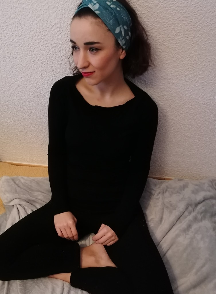Alicia wearing all black (trousers and jumper) sitting cross legged on a grey blanket against a white wall, looking sideways away from camera