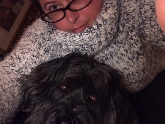 Selfie photo of Alison, wearing light grey knitted jumper, with black dog in the forefront