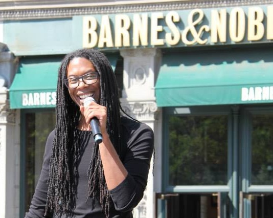 Christopher Sebastian, long dreads  handing mic in left hand, smiling, back ground is shop with sign 'barnes & Nobles'.