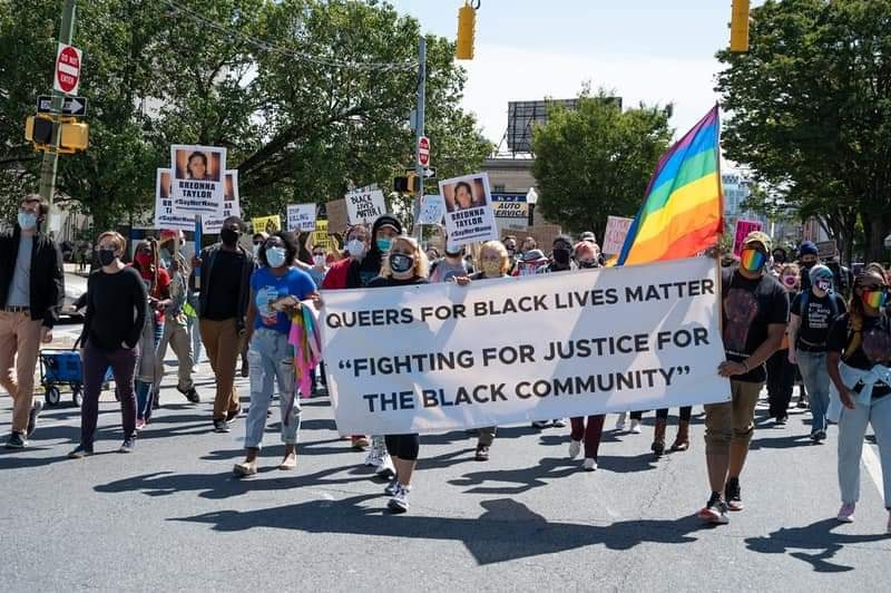 "[alt txt: Photo of a demonstration, several people marching, holding up signs with the name of Breonna Taylor, one person holding a rainbow flag.    Two people in front holding a larger vertical banner. Banner reads: QUEERS FOR BLACK LIVES MATTER. FIGHTING FOR JUSTICE FOR THE BLACK COMMUNITY""]"