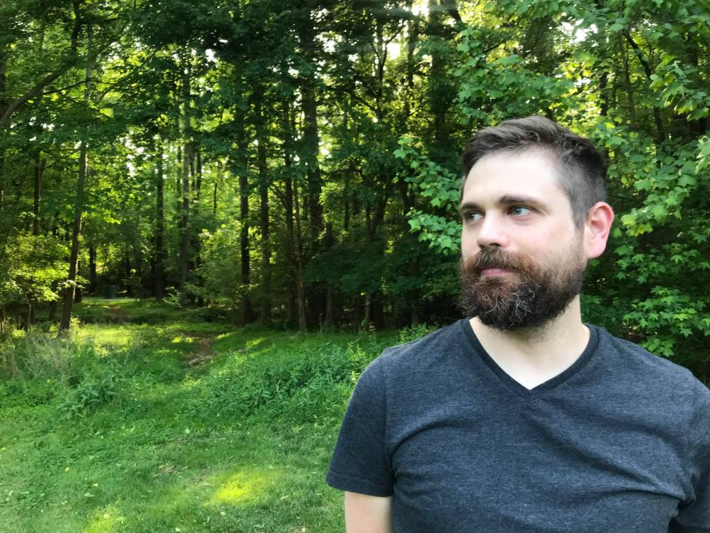 Person wearing grey V-Tshirt, black beard and moustache, facing camera, looking sideways, lots of green foliage and trees in background.