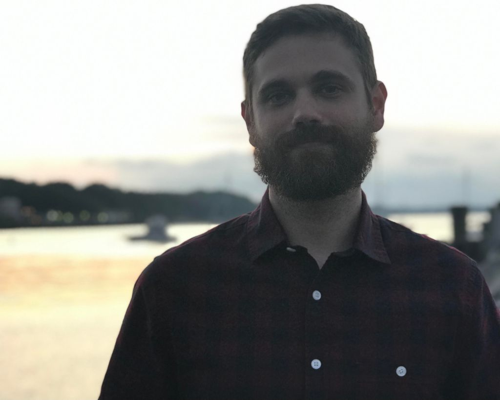 photo of person wearing dark shirt, dark beard and moustache, bright background (appearing to be a sea / lake)