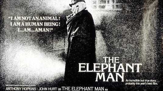 """Black and white poster announcing the movie """"The Elephant Man."""" An incredible but true story .. probably this year's best film.   Phot of a person standing with pale hood over head and hat, and draped in a coat. Text next to person reads: """" I am not an animal! I am a human being! I ... am .. a man!"""".  Anthony hopkins John hurt as the elephant man."""