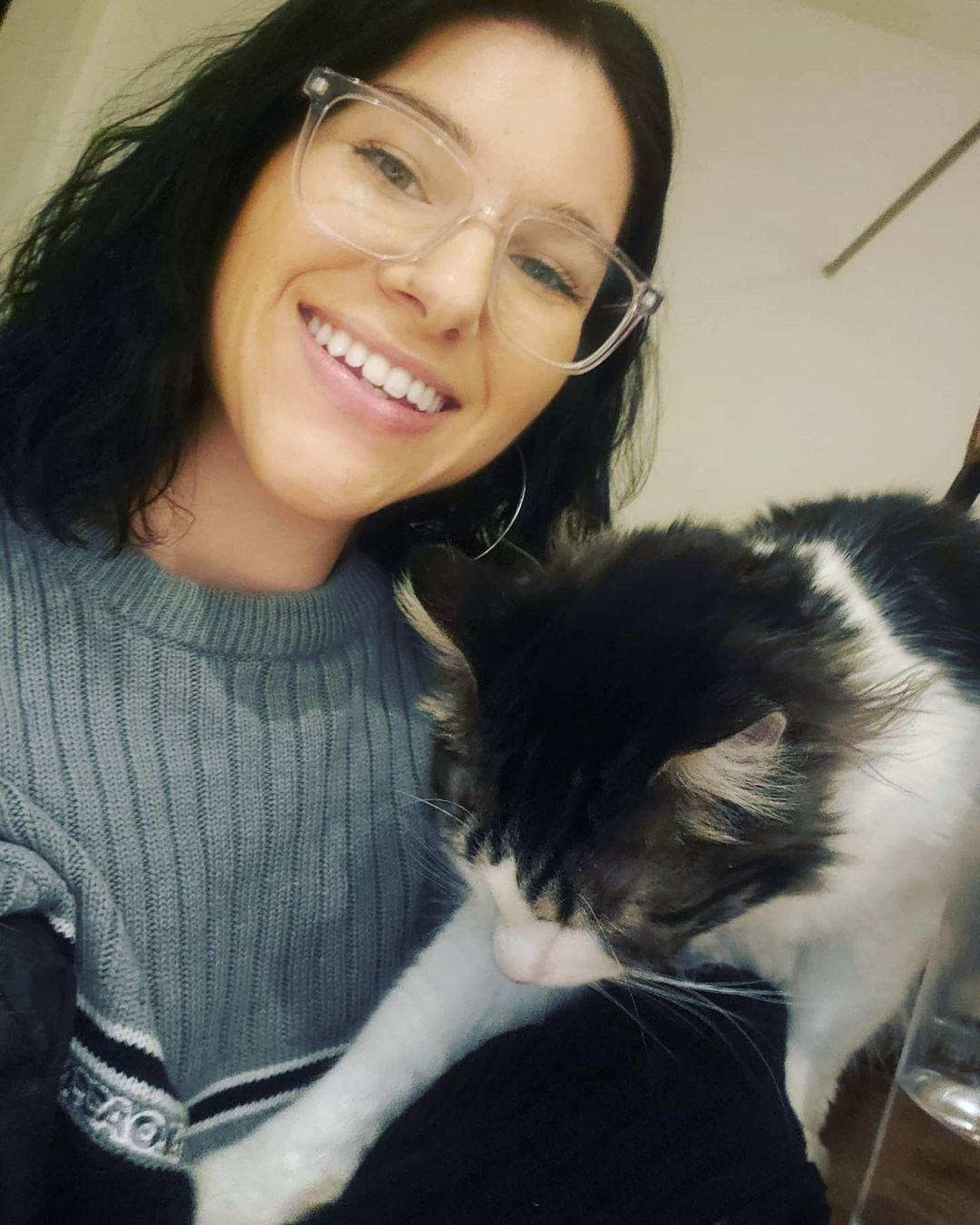 Vanessa smiling, wearing glasses, looking into camera, head slightly tilted, black/grey and white cat coming onto her lap